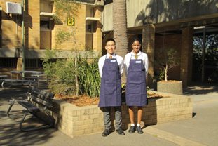 Two industrial arts students standing in front of the building.